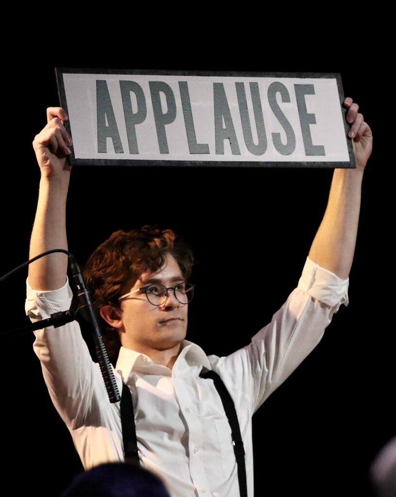 """Student actor in white shirt and black suspenders holds a sign that reads """"APPLAUSE"""" overhead as part of a radio theater production produced by Lafayette College Theater"""